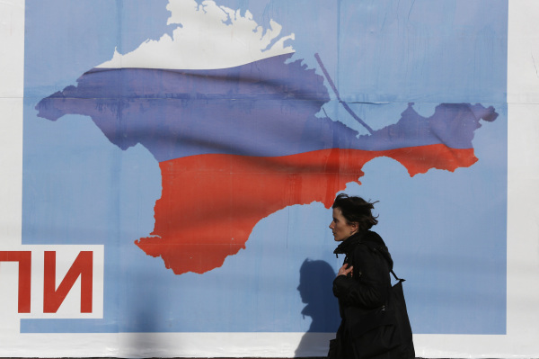 Woman walks by a poster in the Crimean port city of Sevastopol