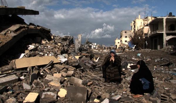 Foto di www.massimozamboni.it - donne siedono sulle macerie delle loro case dopo Piombo Fuso