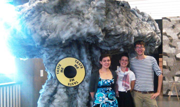 Emma Pritchard, Marie Cucurella e Simon Ott em frente a uma escultura da Bomba Atômica exibida na conferência.