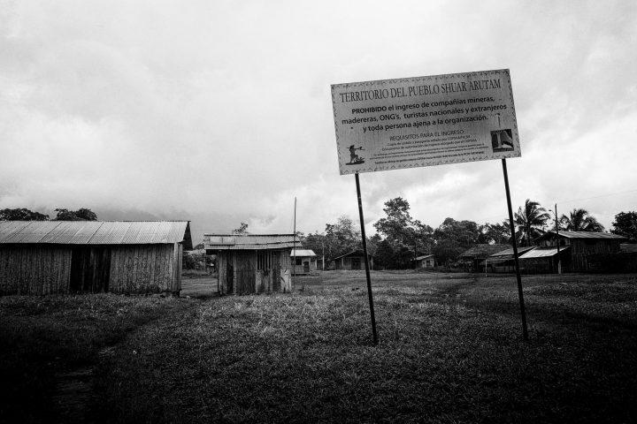 Entrada a la Comunidad shuar de Mayáik, Provincia de Morona Santiago, Ecuador. Cada comunidad ligada a la Federación Interprovincial de Centros Shuar (FICSH), expone un cartel de prohibición de acceso a compañías mineras, madereras, ONG's y turistas en el territorio shuar y adentro de las comunidades. La FICSH fue establecida en 1965 como una organización apolítica y gestiona y controla el territorio shuar en su defensa y preservación.