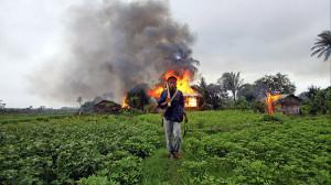 An ethnic Rakhine man holds homemade weapons as he walks in front of houses that were burnt during fighting between Buddhist Rakhine and Muslim Rohingya communities in Sittwe