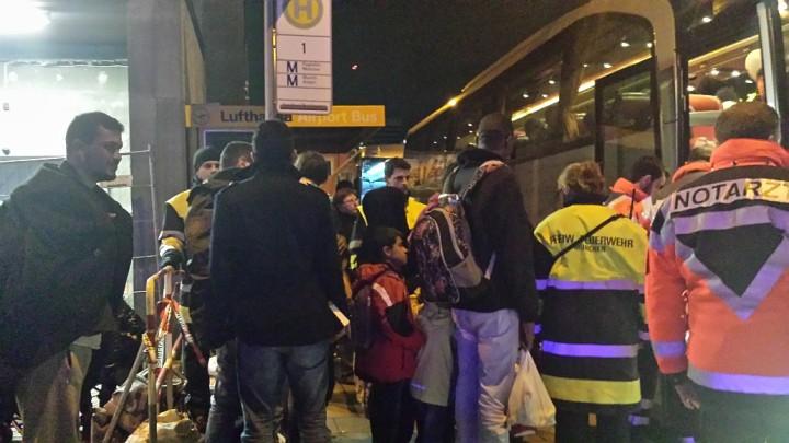 Flüchtlinge beim Besteigen eines Busses, der sie zu ihrer Unterkunft bringen wird. Auch Ärzte und freiwillige Feuerwehr kümmern sich um die Flüchtlinge.