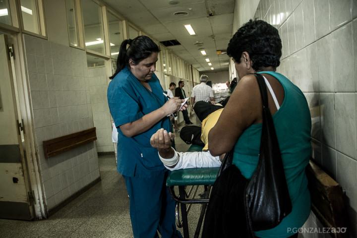 """Por falta de personal y espacio, muchas veces los pasillos se convierten en """"consultorios"""": en medio del tránsito, los médicos atienden a los pacientes."""
