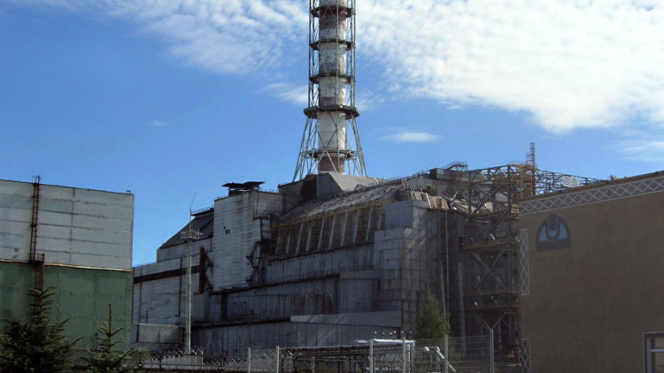 The Chernobyl reactor #4 building as of 2006, including the later-built sarcophagus and elements of the maximum-security perimeter.