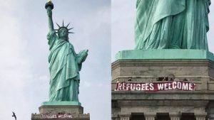 """Attivisti espongono uno striscione """"Refugees Welcome"""" sulla Statua della Libertà"""
