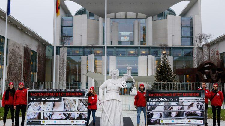 Protestaktion in Berlin gegen die illegale und tierquälerische Kastenstandhaltung von Muttersauen: Bundeslandwirtschaftsministerin will das bereits 2015 ergangene Urteil einfach umgehen und die Kastenstandhaltung für weitere 17 Jahre verlängern.