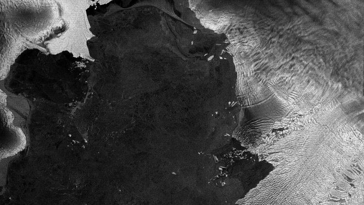 Vista desde el satélite Envisat: Pine Island (parte central de arriba) y el glaciar Thwaites (parte inferior derecha), los dos glaciares antárticos que se desplazan a mayor velocidad que cualquier otro glaciar en la Antártida. Se muestran tal y como fueron vistos el 15 de agosto de 2011 por el radar ASAR de la Agencia Espacial Europea (ESA). Un iceberg identificado como B-22A, se separó del glaciar Thwaites hace pocos años, pero se mantiene cerca como si hubiese sido anclado a un banco submarino. Este iceberg mide 80×45 km, y el tamaño de la imagen captada por Envisat es de 226×335 km.