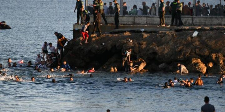 Migrants swimming around the Tarajal spur