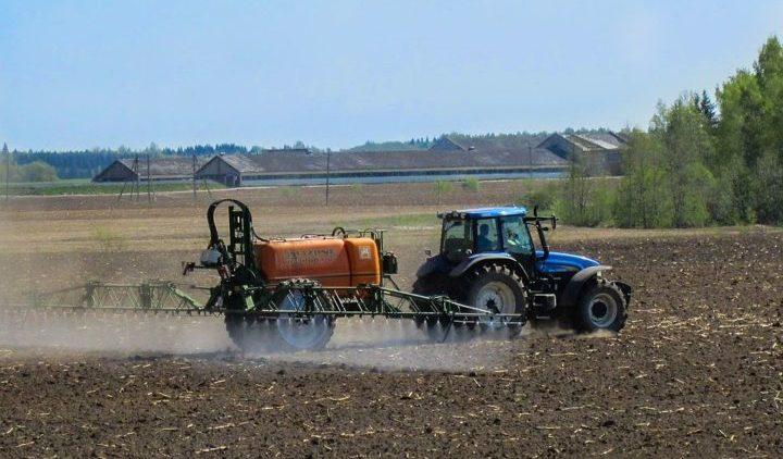 Tractor rociando pesticidas en el campo.