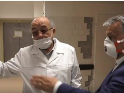 """Prime Minister Orban in early April visiting the Budapest Korányi Institute of Pulmonology - a clinic with specific responsibility for Covid-19 patients. In the background are some indications of disrepair including tiles falling off the wall and an """"out of order"""" sign on the elevator."""