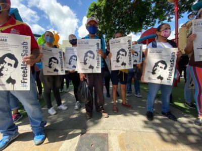 Demonstrators hold up signs calling for the release of Alex Saab.