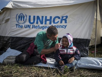 """Mahmoud, a syrian refugee from Aleppo, plays with his son, Jawad, 4, in front of a tent built by UNHCR where they live with the rest of the family since they crossed the hungarian border from Serbia, on september 13, 2015. Mahmoud said that he """"didn't want to wake up in a tent but in a bed like a real person"""". Thousands of refugees, most of them from Syria, cross the hungarian border everyday with the hope to reach european countries like Sweden or Germany. The next step for them will be to register in Hungary before continuing their long journey."""